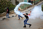 A Palestinian protester hurls back a tear gas canister during clashes with Israeli security forces next to the Jewish settlement of Psagot, near the West Bank city of Ramallah, November 3, 2015. The current wave of violence erupted in mid-September, fueled by rumors that Israel was trying to increase Jewish presence in Jerusalem then quickly spread across Israel, the West Bank and the Gaza Strip. Photo by Shadi Hatem