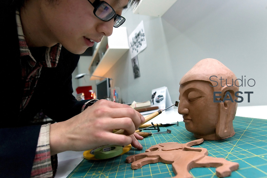 Peugeot clay modeler Li Xiang pratices on a Buddah hear in PSA Peugeot Citroen China Tech Center in the outskirts of Shanghai, China, on April 9, 2010. Car models are made out of clay, therefore PSA Peugeot Citroen Tech Center uses clay modelers. Photo by Lucas Schifres/Pictobank