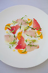 A fresh sashimi dish at Roy's Restaurant Waikiki using only local ingredients.  Bigeye Tuna, Kona Kampachi from the Big Island, Kahuku Sea Asparagus, Big Island Hearts of Palm, Kau Oranges, Nursery Farm Micro Cilantro and Yuzu