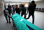 Palestinians carry the body of Qassem Sabaneh, a twenty-year-old man who was shot dead after allegedly trying to stab Israeli police at the Tapuah junction, as they arrive at a hospital in the nearby West Bank city of Nablus, on October 30, 2015. Two Palestinians allegedly tried to stab Israeli police at the West Bank checkpoint, one of whom was shot dead while the other was wounded by Israeli fire, police said. Photo by Nedal Eshtayah