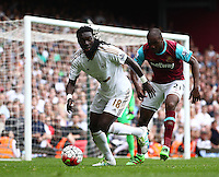 Bafetimbi Gomis of Swansea ans Angelo Ogbonna of West Ham United   during the Barclays Premier League match between West Ham United and Swansea City  played at Boleyn Ground , London on 7th May 2016