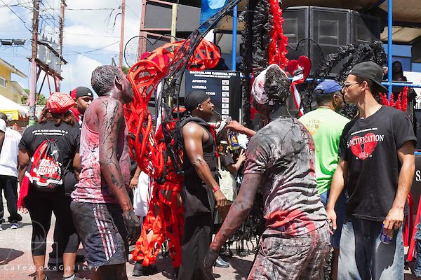 "Trinidad Carnival 2012, Brian Macfarlane's band 'Sanctification"" Mud mas men from Jouvay watch and play as the  band passes"