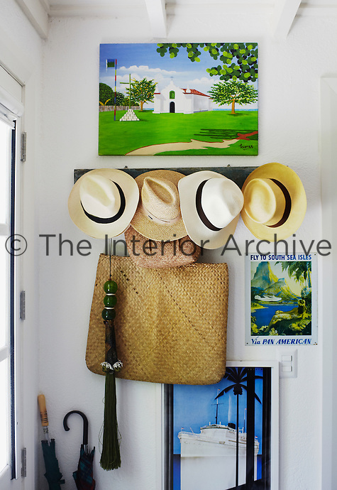 A collection of Panama hats hangs in the entrance hall beside the front door