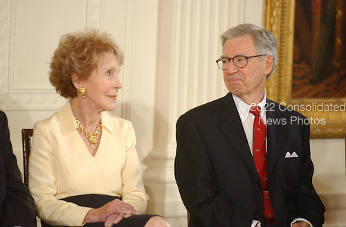 Washington, DC - July 9, 2002 -- Former First Lady Nancy Reagan and Fred Rogers exchange smiles as U.S. President George W. Bush honors them as recipients of the Presidential Medal of Freedom during a ceremony in the East Room of the White House on 9 July, 2002.<br /> Credit: Ron Sachs / CNP