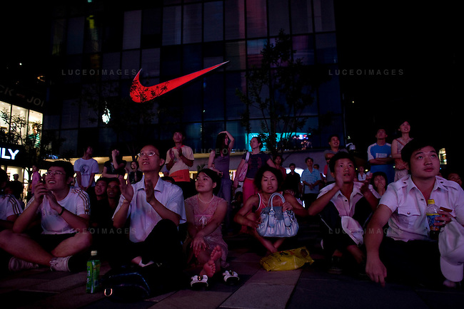 Locals watch the Olympics on a large TV screen at the Adidas store in Beijing, China on Tuesday, August 19, 2008.  Kevin German