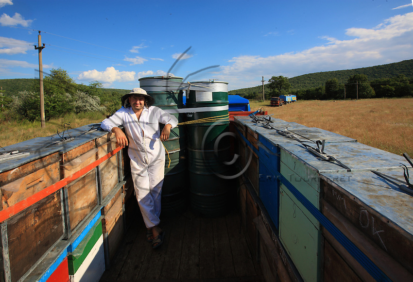 Onéa Dinu Calin on his truck surrounded by hives and the barrels in which he stores the linden flower honey to sell to his customers in Maramures.
