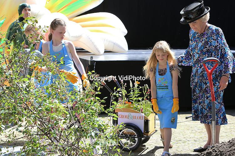 """DELFT – Prinses Beatrix heeft woensdag op het Sint Agathaplein in Delft het startsein gegeven voor de Nationale Tuinweek van Groei & Bloei. Dat deed zij door samen met Delftse schoolkinderen een krentenboompje te planten op het plein. Daarna kreeg ze een rondleiding langs een aantal bakfietsen met daarin verschillende streekgebonden bloemen en planten. Thema voor de Nationale Tuinweek is """"Tegel er uit, plant er in."""" De tuinweek, een initiatief van vereniging Groei & Bloei, wordt dit jaar voor het eerst gehouden. De grootste tuinvereniging van Nederland en België wil hiermee meer mensen enthousiast maken om actief te gaan tuinieren met bloemen en planten. In het weekend van 21 juni wordt het evenement afgesloten met het nationale Open Tuinenweekend, waarin meer dan 1000 tuinbezitters hun tuin gratis open stellen voor publiek."""