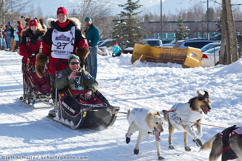 Aliy Zirkle and team run past spectators on the bike/ski trail during the Anchorage ceremonial start during the 2013 Iditarod race.    Photo by Britt Coon/IditarodPhotos.com