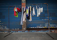 Laundry hangs in front of a shuttered shop near the Yue Yuen Industrial Holdings Limited factory in Dongguan, Guangdong Province, China, 03 March 2015.