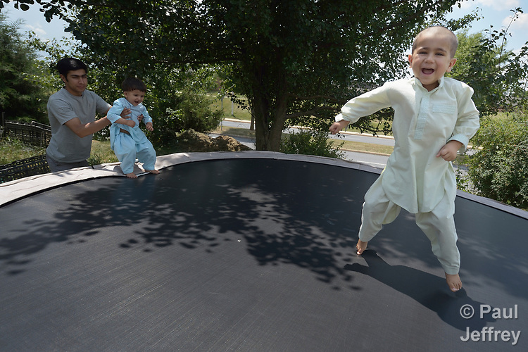 Nasratullah Ahmadzai, 4, bounces on a trampoline as his brother, Sanaullah Ahmadzai, 2, gets a boost from their father, Ahmadullah Ahmadzai, in the yard of their home in Harrisonburg, Virginia. Refugees from Afghanistan, they were resettled in Harrisonburg by Church World Service.<br /> <br /> Photo by Paul Jeffrey for Church World Service.