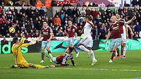 Pictured: Wayne Routledge of Swansea (in white) has his shot stoped by Adrian (L) goalkeeper for West Ham Saturday 10 January 2015<br />