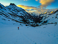 A lone skier skins up Yankee Boy Basin near Ouray, Colorado as the sun's first rays illuminate the clouds and peak tops behind him.