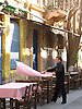 A man sets cafe tables on a tiny street in the Plaka neighborhood of Athens, Greece. Photo by Kevin J. Miyazaki/Redux