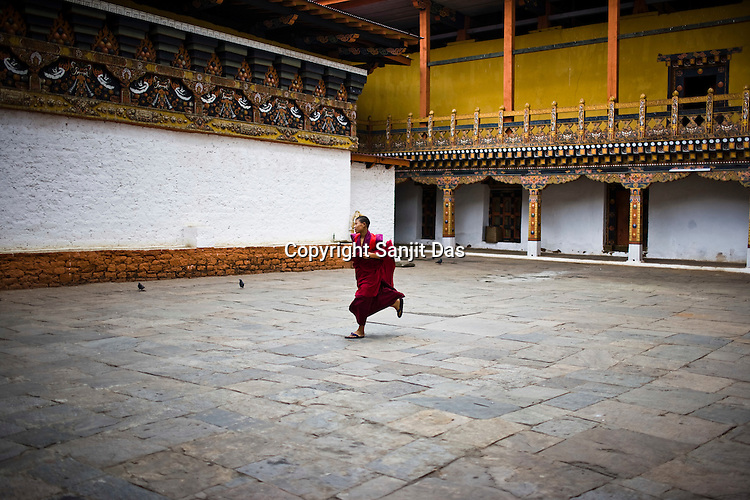 A Buddhist monk runs to attend the prayers inside the Punakha Dzong (fortress) in Punakha, Bhutan. Phunakha was the capital of Bhutan and the seat of government until 1955, when the capital was moved to Thimphu. Punakha is the administrative centre of Punakha dzongkhag, one of the 20 districts of Bhutan. Photo: Sanjit Das/Panos
