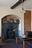 In the living room warmth comes from an old-fashioned wood-burning stove situated in a fireplace tucked into a brick-lined alcove