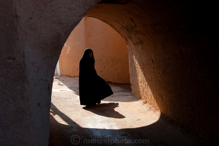 Shielded from the sun and strangers' eyes, and wrapped up against the chilly December air, a woman cloaked in a black chador wends her way through the ancient streets in the old market district of Yazd, Iran. (From the book What I Eat: Around the World in 80 Diets.)