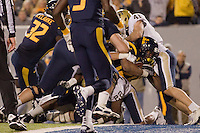 WVU running back Shawne Alston scores on an 8-yard touchdown run.The WVU Mountaineers beat the Pitt Panthers 21-20 at Mountaineer Field in Morgantown, West Virginia on November 25, 2011.