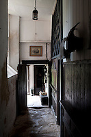 The wood-panelled corridor leading to the back door is lined with ancient flagstones, worn over time and polished by the passing of many feet