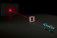 DIFFRACTION OF LASER LIGHT ON SINGLE HUMAN HAIR<br /> A Laser is Used to Determine Width of Human Hair<br /> A laser pointer is used to project a laser beam that is diffracted around a single human hair mounted to a cardboard frame. Both the laser pointer and the frame that holds the laser are supported by binder clips.