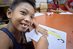 A boy enjoys coloring a picture in Knox United Methodist Church in Manila, Philippines. The church offers food, showers, and fellowship to hungry people in its neighborhood. Included is an educational opportunity for children.