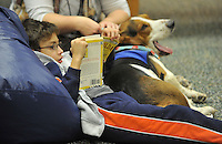 NWA Democrat-Gazette/Michael Woods --01/14/2015-- w @NWAMICHAELW... Luis Cruz, age 9 from Springdale, reads a book to Banjo, a therapy dog, during Wednesday evenings session of the Kibbles and Books program at the Springdale Public Library. Kibbles & Books is a literacy program designed to build confidence in young readers by reading out loud to therapy dogs giving the children a chance to practice their literacy skills in a stress-free and fun context.