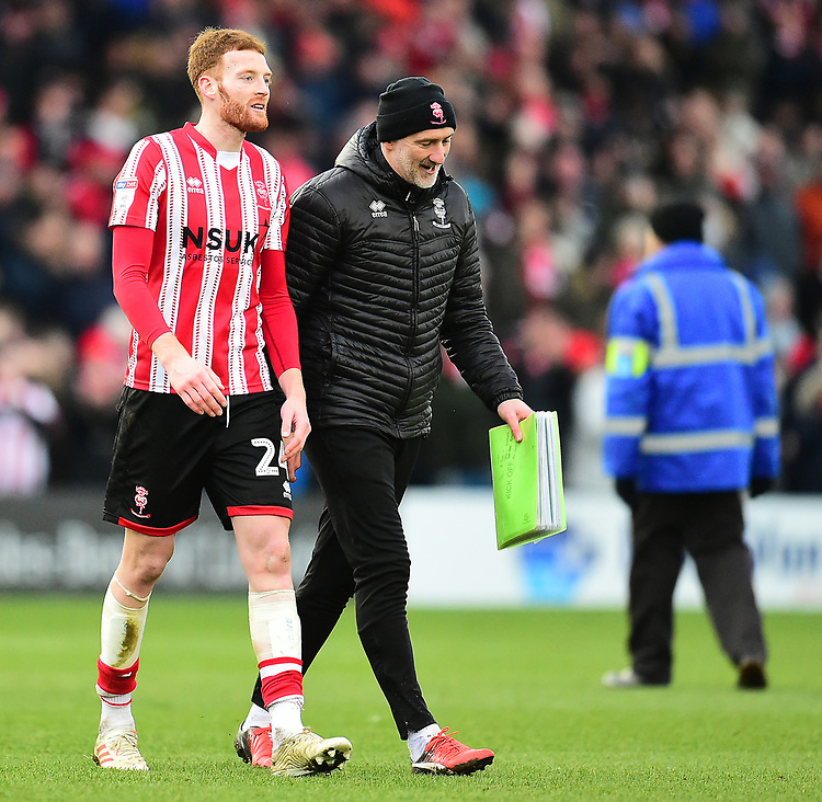 Lincoln City's Cian Bolger, left, and Lincoln City's first team goalkeeping coach Andy Warrington at the end of the game<br /> <br /> Photographer Andrew Vaughan/CameraSport<br /> <br /> The EFL Sky Bet League Two - Lincoln City v Grimsby Town - Saturday 19 January 2019 - Sincil Bank - Lincoln<br /> <br /> World Copyright &copy; 2019 CameraSport. All rights reserved. 43 Linden Ave. Countesthorpe. Leicester. England. LE8 5PG - Tel: +44 (0) 116 277 4147 - admin@camerasport.com - www.camerasport.com