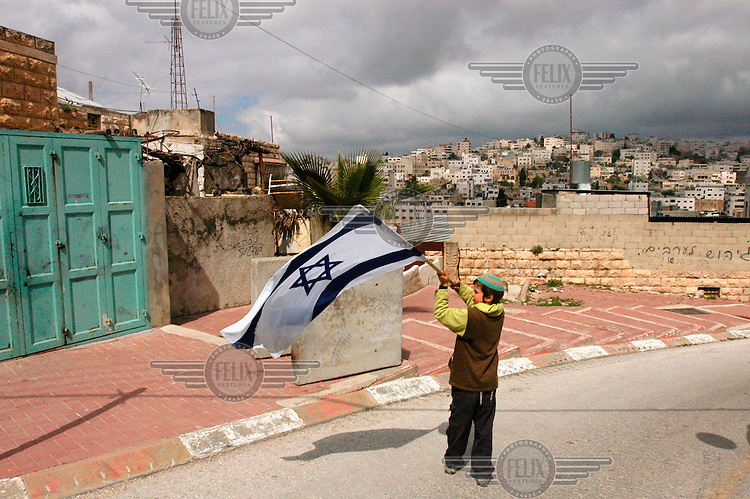 A child waves the Israeli flag in front of the Palestinian part of the city, during the traditional Purim march of the Jewish settlers, in the city of Hebron.