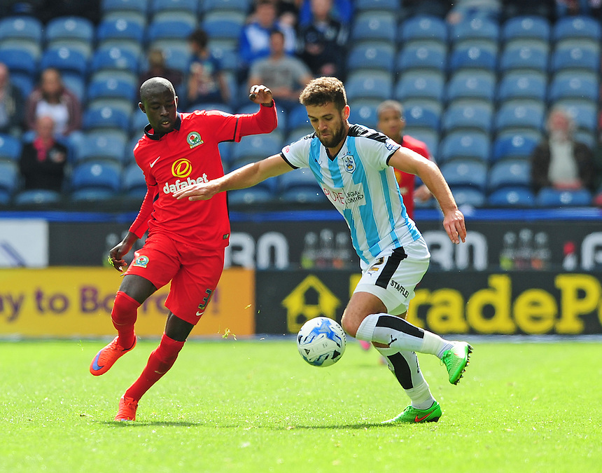 Blackburn Rovers&rsquo; Modou Barrow vies for possession with Huddersfield Town's Tommy Smith<br /> <br /> Photographer Chris Vaughan/CameraSport<br /> <br /> Football - The Football League Sky Bet Championship - Huddersfield Town v Blackburn Rovers - Saturday 15th August 2015 - The John Smith's Stadium - Huddersfield<br /> <br /> &copy; CameraSport - 43 Linden Ave. Countesthorpe. Leicester. England. LE8 5PG - Tel: +44 (0) 116 277 4147 - admin@camerasport.com - www.camerasport.com