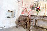 Building interior details medieval sanctuary with aumbry niche, fragments of 13th century painted reredos, simple communion altar with crucifix, vase of flowers, multiple layers of paint on wall church architectural features, Inglesham, Wiltshire, England
