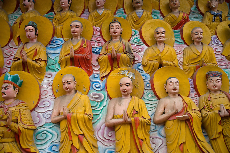 Buddha sculptures decorate a wall at the Holy Water Temple in Mianyang, Sichuan, China.