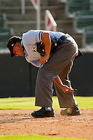Home plate umpire Jose Esteras cleans off the plate during the game between the Delmarva Shorebirds and the Kannapolis Intimidators at Fieldcrest Cannon Stadium on August 7, 2011 in Kannapolis, North Carolina.  The Intimidators defeated the Shorebirds 8-3.   (Brian Westerholt / Four Seam Images)