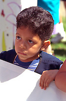Introspective boy age 5. In the Heart of the Beast May Day Festival and Parade Minneapolis  Minnesota USA
