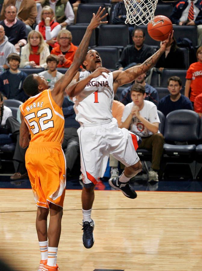 Virginia guard Jontel Evans (1) shoots next to Tennessee guard Jordan McRae (52) during the game Wednesday in Charlottesville, VA. Virginia defeated Tennessee 46-38.
