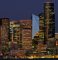 Concentrated cityscape of downtown Seattle skyscrapers at night next to Elliott Bay with ferry at dock. Seattle, Washington. Taken in September, 2018.