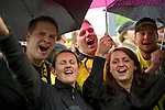 A group of young fans is singing in the rain during the festival with 200000 fans on the festival grond. - In Dortmund fans celebrated a gigantic party because of the title win of their favorite soccer club BVB 09 in the German Premium League.