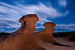 Two eerily shaped rock formations appear to guard a lonely path through Goblin Valley State Park, near Hanksville, Utah