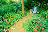 Blue painted adirondack chair at the end of the shade garden path. It sits beside a matching painted birdhouse and is complimented by blooming flowers