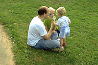 Dad age 35 sharing cone at Lake Harriet Park with son and daughter ages 4 and 2.  Minneapolis Minnesota USA