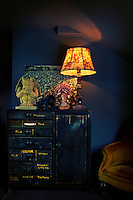 A table lamp with a red floral shade and a impish figures are placed on a cupboard with a distressed paint finish. The lit lamp illuminates the dark blue room.