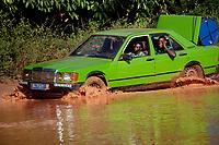 A group of men attempt to drive a Mercedes Benz car through a river.
