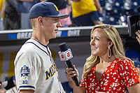 Michigan Wolverines first baseman Jimmy Kerr (15) is interviewed by ESPN reporter Chris Budden after beating the Vanderbilt Commodores in Game 1 of the NCAA College World Series Finals on June 24, 2019 at TD Ameritrade Park in Omaha, Nebraska. Michigan defeated Vanderbilt 7-4. (Andrew Woolley/Four Seam Images)