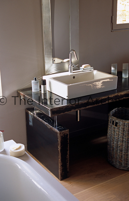 A rectangular porcelain wash basin has been placed on top of a distressed metal washstand in the bathroom