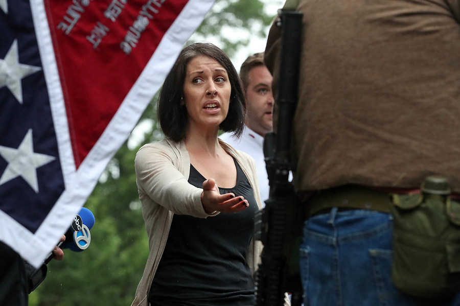 Charlottesville resident Lara Rogers points to a gun worn by Allen Armentrout of North Carolina who stood protecting the Lee Statue Tuesday, Aug. 15, 2017 at Emancipation Park in Charlottesville, Va. A small crowd of Charlottesville residents protested him for 30 minutes before Police escorted Armentrout away from the park. Photo/Andrew Shurtleff