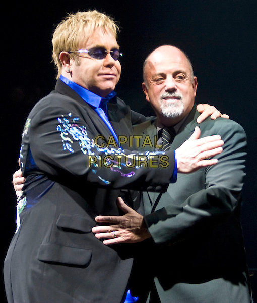 SIR ELTON JOHN & BILLY JOEL .Elton John and Billy Joel - Face 2 Face Tour held at U.S. Bank Arena, Cincinnati, Ohio, USA, .10 March 2009..to concert music gig live performing in concert half length goatee facial hair  microphone beard  black embroidered blue shirt tinted glasses hugging .CAP/ADM/BP.©Keith Klenowski/Admedia/Capital PIctures