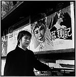 Pg 24 - Li's first love, Sun Peikui, in front of a billboard advertising a Chinese opera-based film entitled Lychee Mirror in Harbin, Heilongjiang province. 26 August 1966