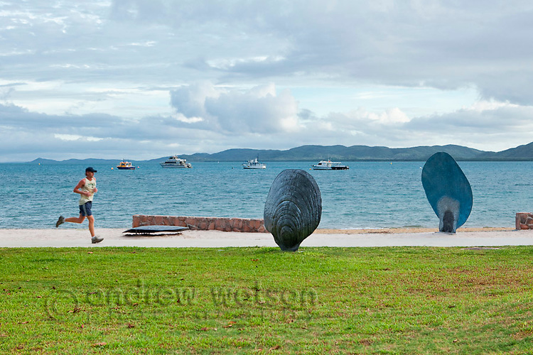 Jogger and public artworks on the Victoria Parade foreshore.   Thursday Island, Torres Strait Islands, Queensland, Australia