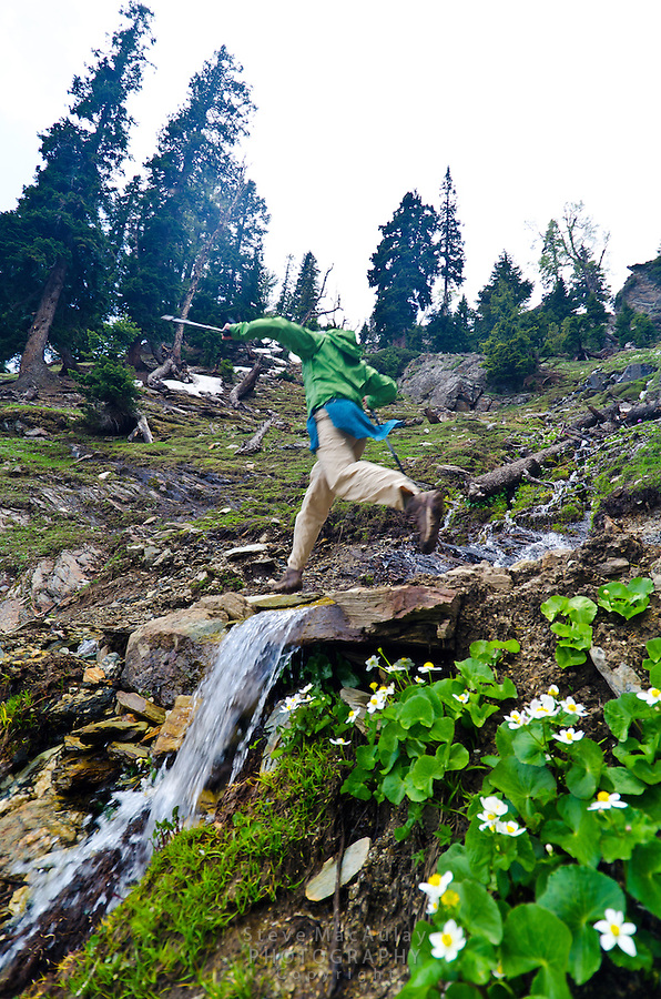 Leaping across a steep creek while trekking in the Himalaya Mountains of Kashmir India.