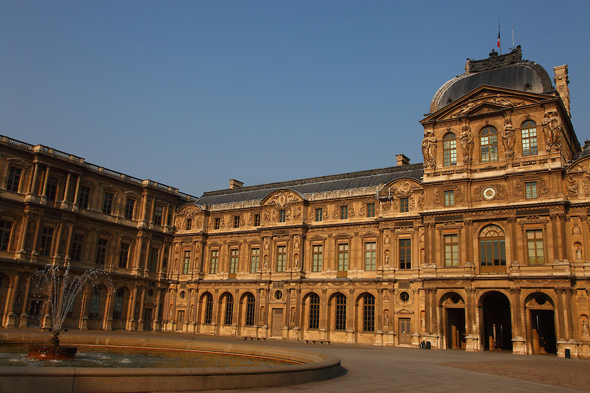 A view of the Cour Carrée with its fountain with water, with the most ancient corner of the Louvre (on the left) and the façade of the Pavillon of the Clock (the other side of the Pavillon Sully). Digitally Improved Photo.