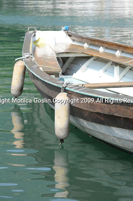 A white and brown wooden boat on Lake Como, Italy in the town of Gravedona.