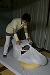A man in darkness is wrapped in cloth during an Otonamaki (adult wrapping) therapy session on February 4, 2017, Tokyo, Japan. Otonamaki is a Japanese therapeutic method to reduce stiffness and posture problems. A participant, monitored by a health care professional is wrapped in a large piece of breathable cloth, like a sheet, to alleviate posture problems and body stiffness for about 15 to 20 minutes. The therapy comes from Ohinamaki, the practice of wrapping up babies in cloth in a similar way to give them a feeling of security and help them with their physical development. (Photo by Rodrigo Reyes Marin/AFLO)